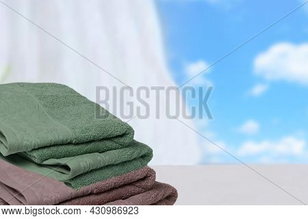 Closeup Of A Stack Or Pile Of Brown And Green Soft Terry Bath Towels On A Light Table On An Abstract