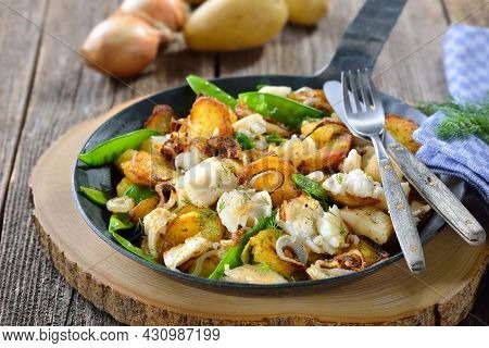 Fried Potatoes With Pieces Of Halibut Fillet, Sugar Peas And Onion Rings, Often Served In A Frying P