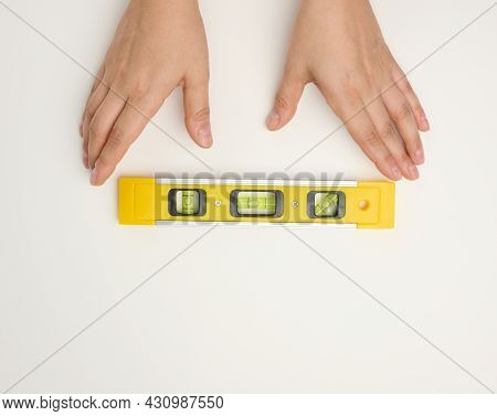 Female Hands Holds A Yellow Plastic Building Level On A White Background. Measuring Instrument Of Re