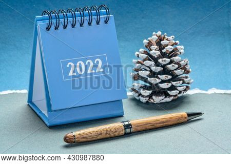 2022 spiral desktop calendar with a decorative frosty pine cone against handmade paper, New Year, time management and business concept