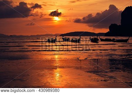 Beautiful Sunset Scene With Dramatic Sky Over Sea Shore Beach With Traditional Longtail Boats In Tha