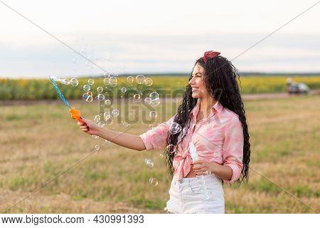 Cute Brunette Woman Blowing Soap Bubbles.