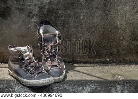 Brown Retro High Top Canvas Sneakers Was Placed On Old Cement Floor. Vintage Age-worn Sneakers Canva