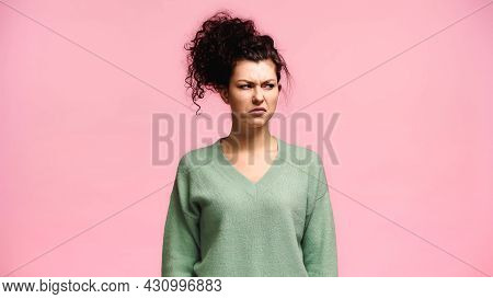 Displeased Woman In Green Pullover Looking Away Isolated On Pink