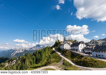 Small And Ancient Village Of Lussari Or Monte Santo Di Lussari (1790 M) And The Peak Of Mangart Moun