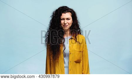 Offended Woman In Orange Shirt Looking At Camera Isolated On Blue