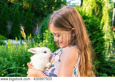 The Girl Is Holding A White Fluffy Hare On Her Chest. Happy Childhood Concept. Pet And Kid Friendshi
