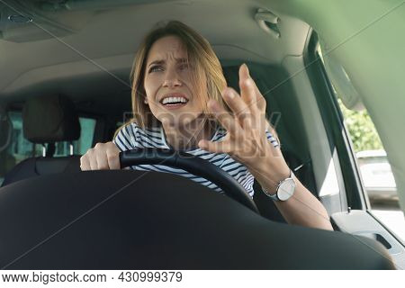 Stressed Angry Woman In Driver's Seat Of Modern Car, View Through Windshield