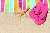 Tropical beach vacation holiday and travel concept with a colourful striped beach towel and vibrant pink sandal flip flip thongs on pristine sand with a starfish at an idyllic coastal beach resort. poster