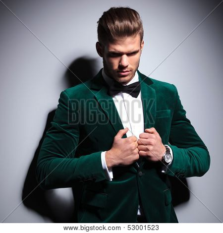 young man in green suit and bow tie looking a little sad on gray background