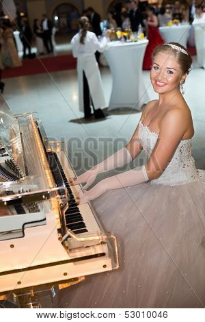 MOSCOW - MAY 25: Beautiful smiling girl in a wedding dress playing the piano at 11th Viennese Ball in Gostiny Dvor on May 25, 2013 in Moscow, Russia.