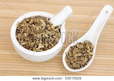 Licorice herb root used in chinese herbal medicine in a mortar with pestle and spoon. Gan cao. Glycyrrhiza glabra.