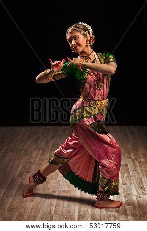 Young beautiful woman dancer exponent of Indian classical dance Bharatanatyam in Krishna pose