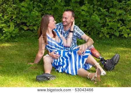 Loving Couple Sitting On The Grass