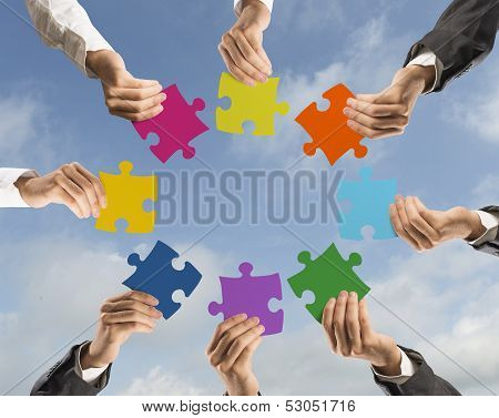 Concept of teamwork and integration with businessman holding colorful puzzle poster