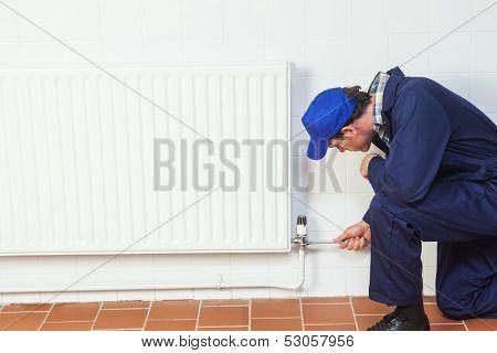 Handyman repairing a radiator in bright room