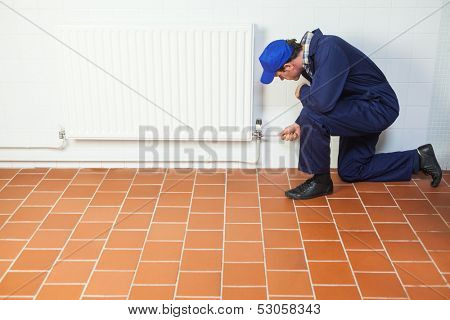 Handyman in blue boiler suit repairing a radiator in bright room