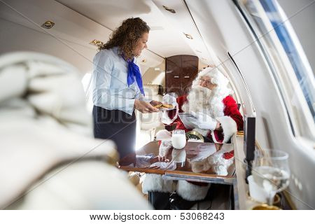 Mid adult airhostess serving cookies to Santa in private jet