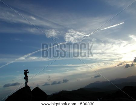 A Man Standing At The Top Of The Mountain