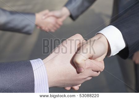 Close up of four business people shaking hands