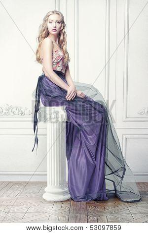 beautiful woman, sitting on the column in luxury interior