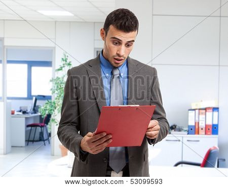 Shocked businessman reading a document poster