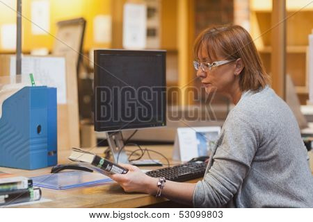 Female librarian holding a book reading the cover before scanning it