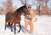 Man dressed in warm clothes putting hay out for horses on a cold snowy winter day poster
