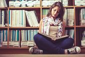 Full length of a female student sitting against bookshelf and reading a book on the library floor poster