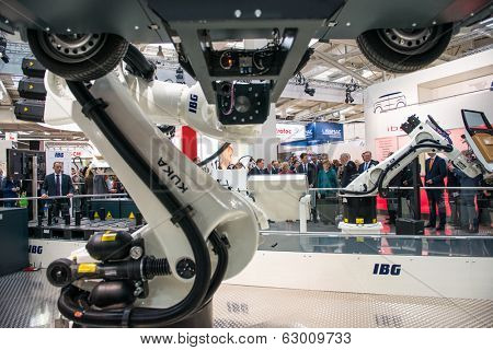 HANOVER, GERMANY - APRIL 7: German Chancellor Angela Merkel during a technology showcase tour of innovations in industrial Robotics used in the Automotive industry, 7 April 2014