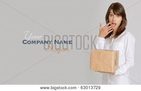 Young woman holding a brown parcel with a surprised expression