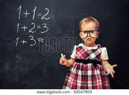 Baby Girl  In Glasses And Chalk At A School Board With Arithmetic Examples