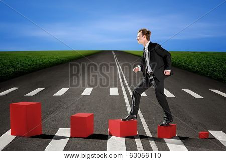 Businessman Walking Up On The Red Boxes On The Road, Means Financial And Career Growth