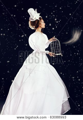 Full length portrait of a beautiful fashion model in the refined white dress and elegant hat. Snow queen. Winter fantasy.