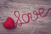 Red heart of red wool yarn on a wooden background poster