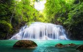 Tropical waterfall in Thailand, nature photography. Fresh water mountain river in wild green jungle forest. Scenic and peaceful Asia nature background of beautiful blue water pool and creek cascade poster