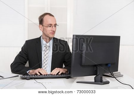 Satisfied conscientious businessman at his office in tie and suit like a lawyer or bookkeeper also an owner of a company