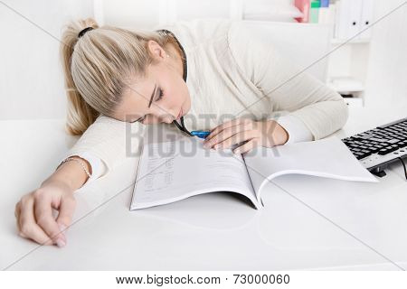 Blonde overworked businesswoman or trainee sleeping at desk over business papers during work time.