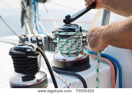 Winch and sailor's hands on sailboat.