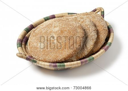 Moroccan semolina bread in a basket on white background