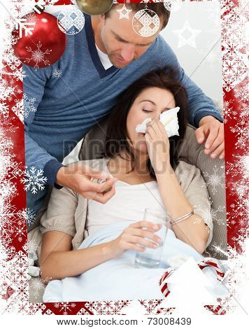 Handsome man taking care of his sick girlfriend against christmas themed frame