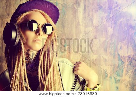 Trendy teenage girl with blonde dreadlocks listening to music on headphones. Jeans style. Modern generation.