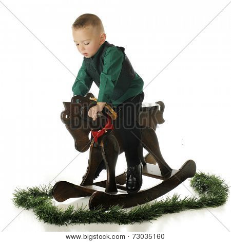 A young preschooler, dressed up for Christmas, riding his gift -- a wooden rocking horse.  On a white background.