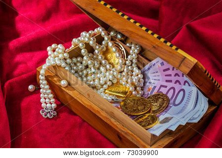 gold coins and bars with decorations on red velvet. symbol photo of wealth, luxury, wealth tax.