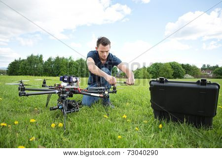 Young technician fixing propeller of UAV helicopter with handtool in park