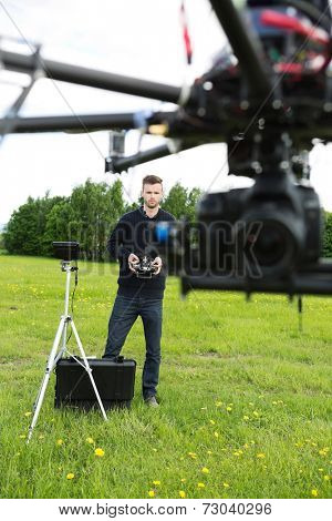 UAV octocopter flying while male engineer operating it in background at park