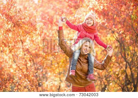 Happy parent and kid walking together outdoor in autumn park. Yellow and red tree leaves. Child sitting on her mother's neck. poster