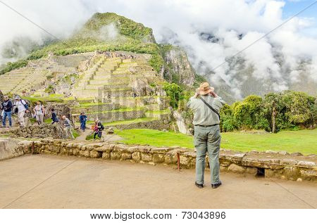 MACHU PICCHU, PERU - MAY 3, 2014 - crowds of tourist explore ruins of old city early in the morning while senior tourist takes photos