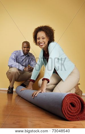 Portrait of couple unrolling carpet