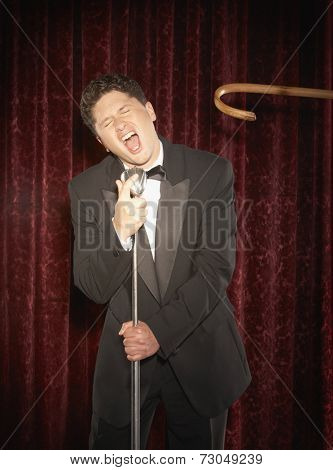 Cane reaching toward male performer with microphone